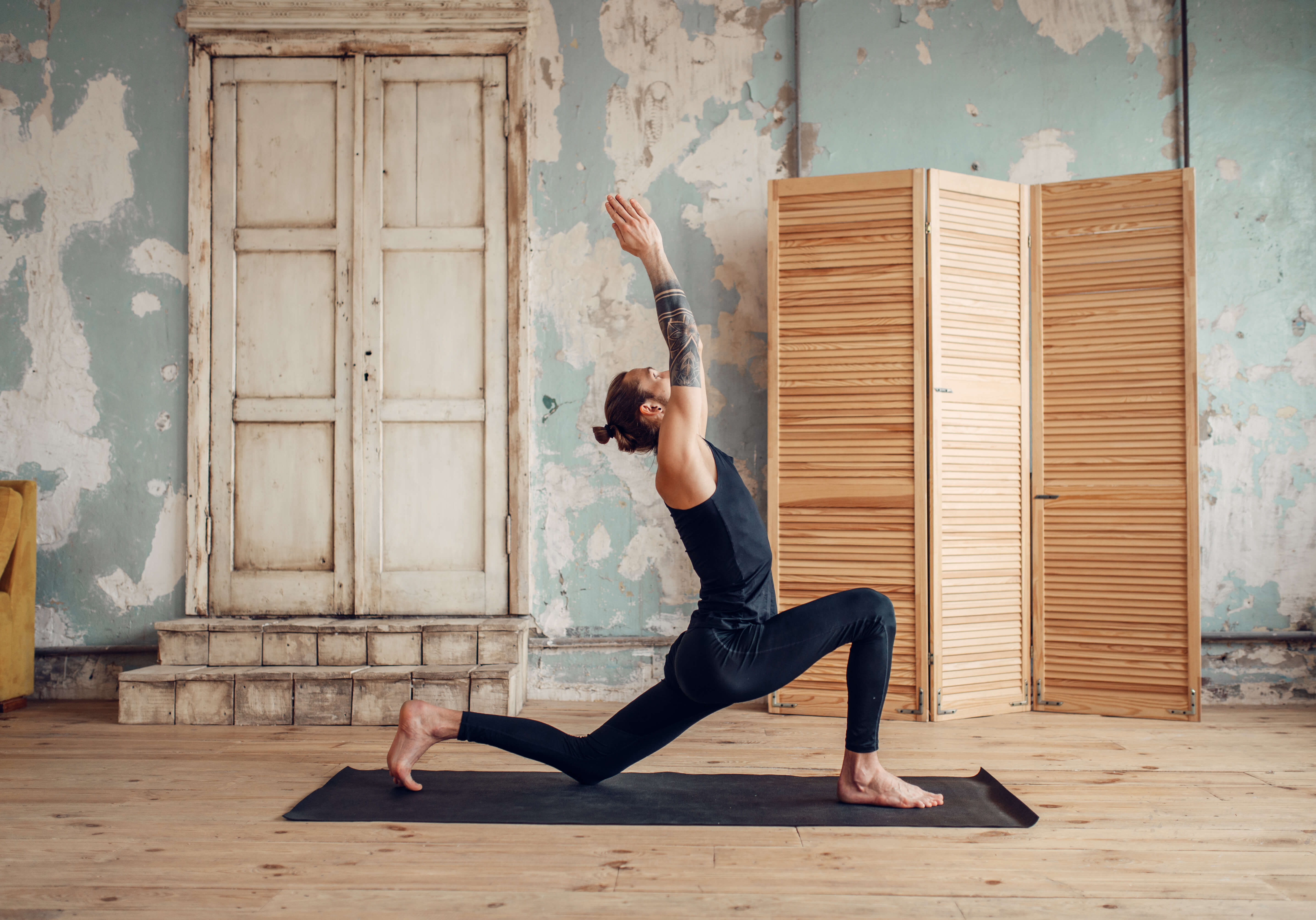 Male yoga with tattoo on hand doing exercise in gym with grunge interior. Fitness training indoors